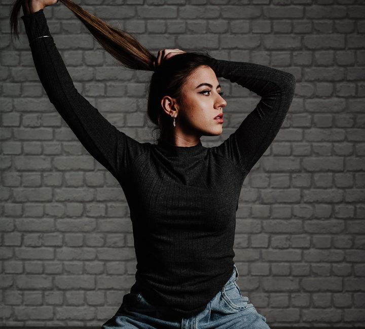 Modelo en estudio sujetándose el pelo