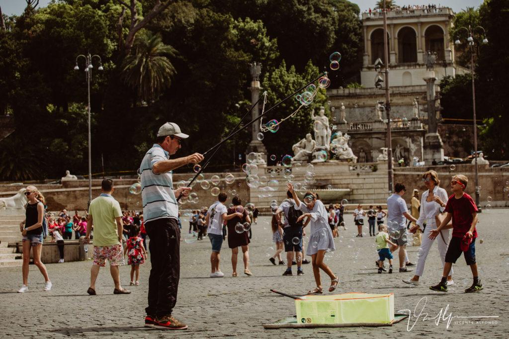 Romano haciendo pompas en una plaza. Paseo fotográfico por la ciudad de Roma